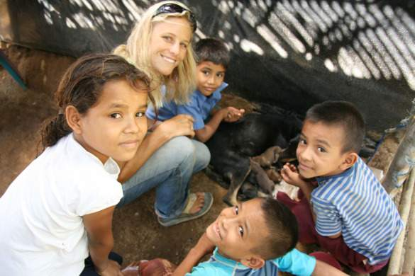 Holly with kids in Nicaragua checking out new puppies