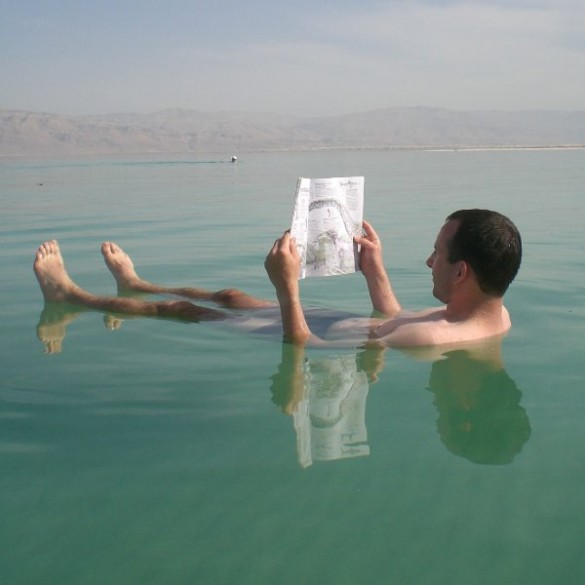 A man reads while floating in the Dead Sea, Ein Gedi, Israel