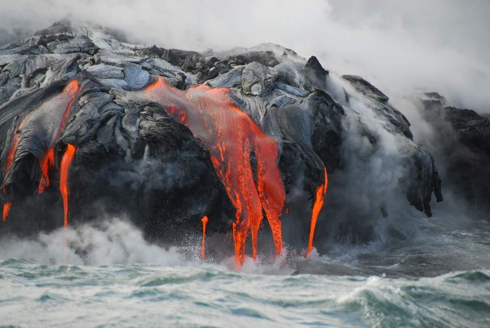 volcanic lava drips into the sea