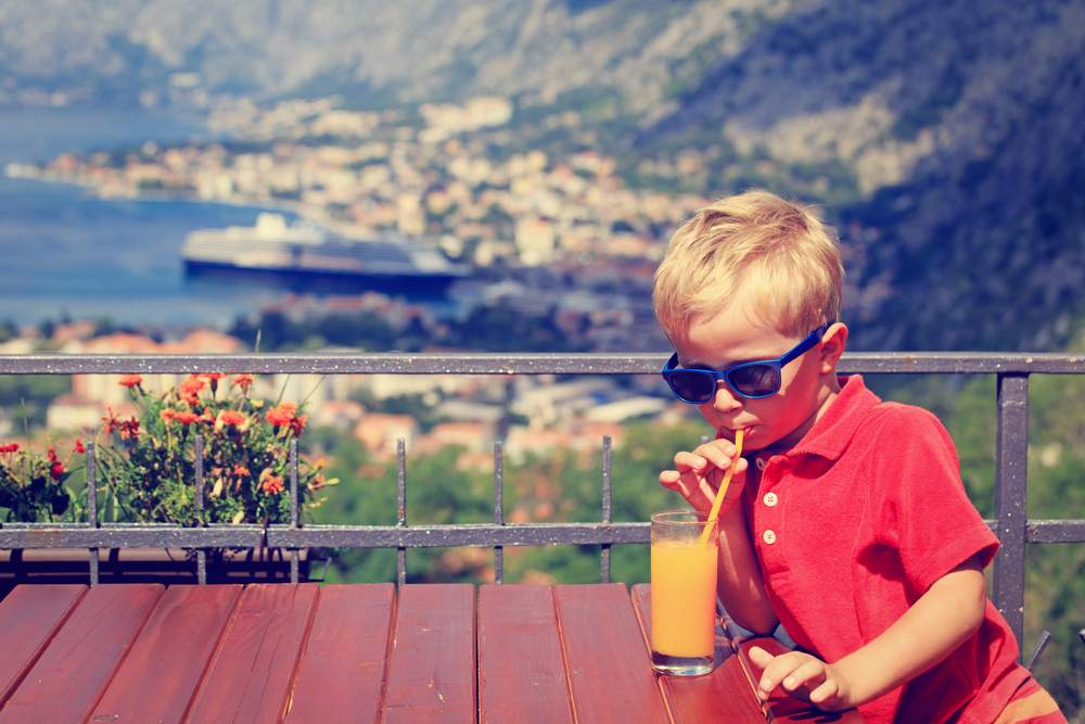 kid in Croatia, drinking juice with a view